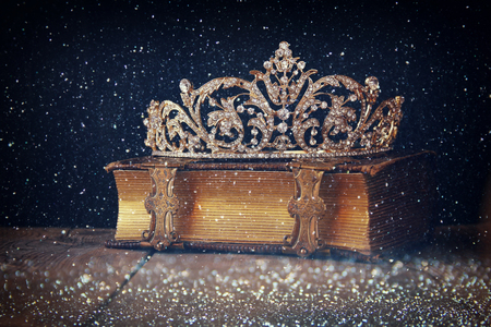 queens: low key image of decorative crown on old book. vintage filtered with flitter overlay. selective focus.