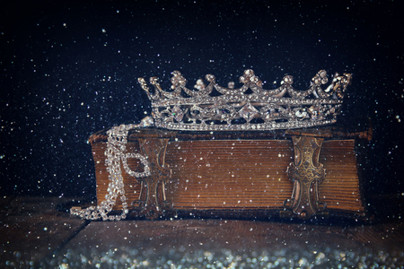 fairytale background: low key image of decorative crown on old book. vintage filtered with flitter overlay. selective focus.