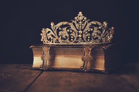 low key image crown on old book. sepia vintage filtered. selective focus