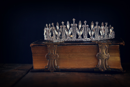 kingdom: low key image crown on old book. vintage filtered. selective focus. Stock Photo
