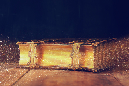 low key image of antique story book. vintage filtered with glitter overlay. selective focus