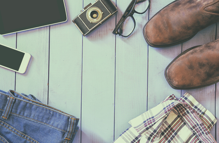 fashion clothes: top view image of hipster accessories and clothes a wooden background. vintage filtered and toned