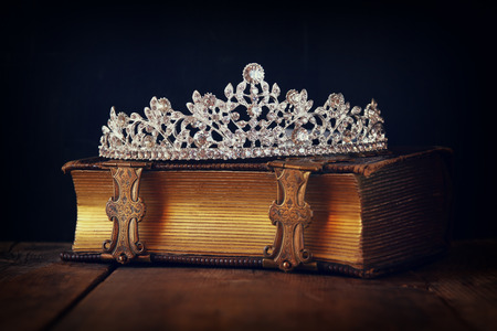 low key image of decorative crown on old book. vintage filtered. selective focus.