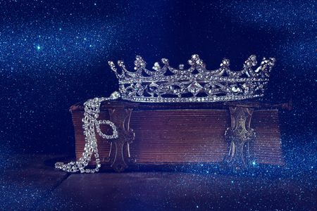 once: low key image of decorative crown on old book. vintage filtered. selective focus.