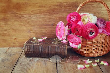 field glass: old book and glasses next to beautiful field flowers on wooden table. vintage filtered. Stock Photo