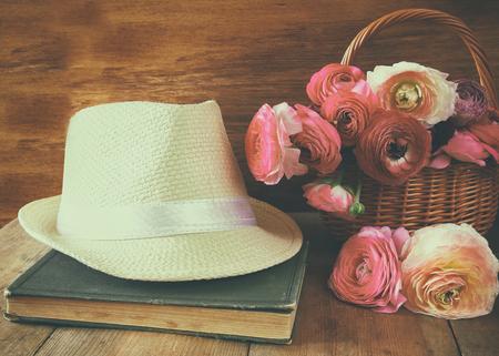 campo de flores: sombrero de ala junto al antiguo libro y flores en la mesa de madera. la vendimia se filtró y tonificado
