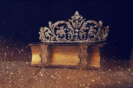 Low key afbeelding van mooie diamant koningin kroon op oud boek. Vintage gefilterd. Selectieve focus