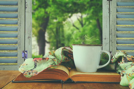 romantic scene of cup of coffee next to old book in front of countryside view outside of the old rustic window. vintage filtered and toned image