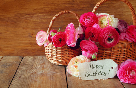 flores de cumpleaños: flores de color rosa en la cesta junto a la tarjeta con la frase: feliz cumpleaños, sobre la mesa de madera.