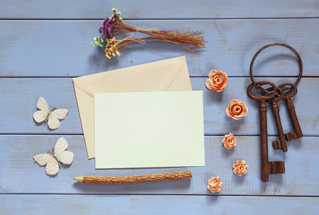 feminine background: vintage mockup with flowers and blank letter on wooden background. vintage filtered and toned