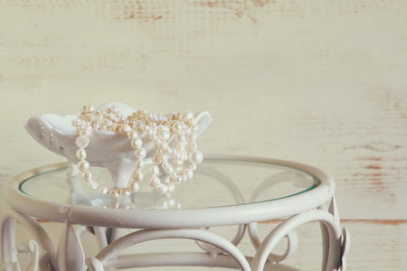 neckless: white pearls necklace on vintage table. vintage filtered. selective focus