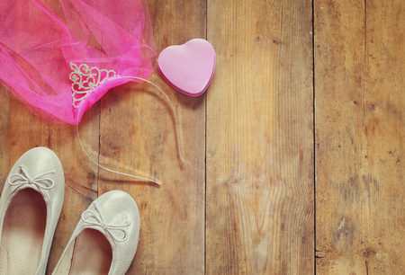 view an elegant wardrobe: girls diamond tiara with pink chiffon vail next to ballet shoes on wooden background. vintage filtered image Stock Photo