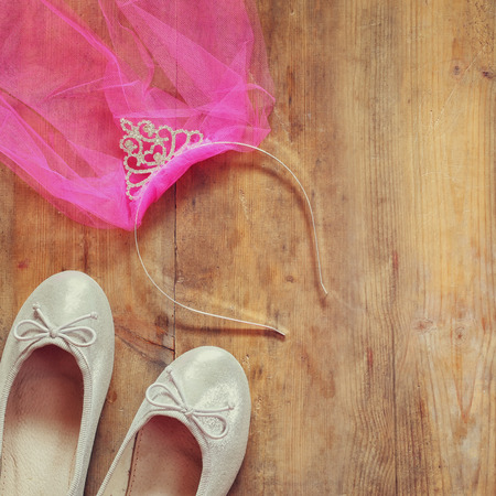 view an elegant wardrobe: girls diamond tiara with pink  chiffon vail next to ballet shoes on wooden background. vintage filtered image