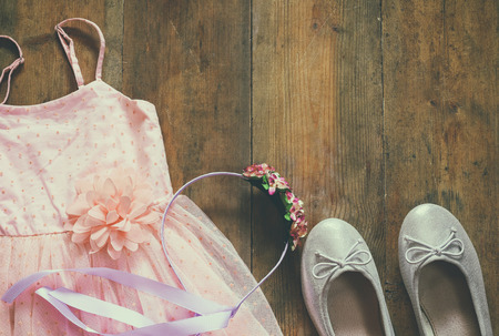 vintage chiffon girls dress, floral tiara next to ballet shoes on wooden background. vintage filtered and toned image