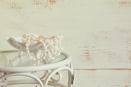 neckless: high key image of white pearls necklace on vintage table. selective focus Stock Photo