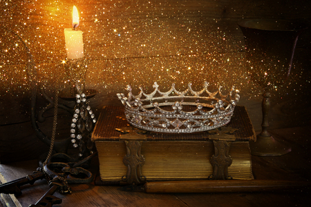 diamond candle: low key image of beautiful diamond queen crown on old book, burning candle. vintage filtered with glitter overlay. fantasy middle age concept Stock Photo