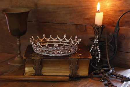 fantasy background: low key image of beautiful diamond queen crown on old book, burning candle. vintage filtered. fantasy middle age concept