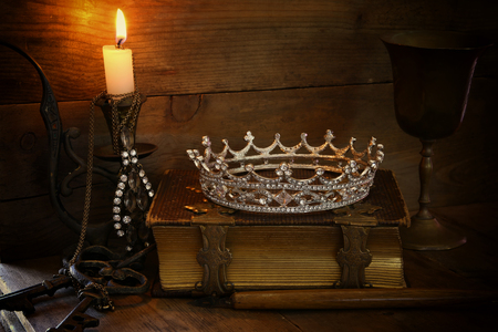 diamond candle: low key image of beautiful diamond queen crown on old book, burning candle. vintage filtered. fantasy middle age concept