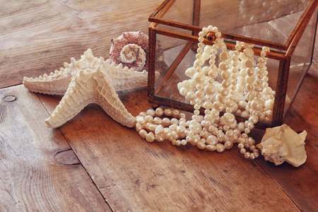 neckless: image of white pearls necklace and seashells on old grunge wooden table. vintage filtered