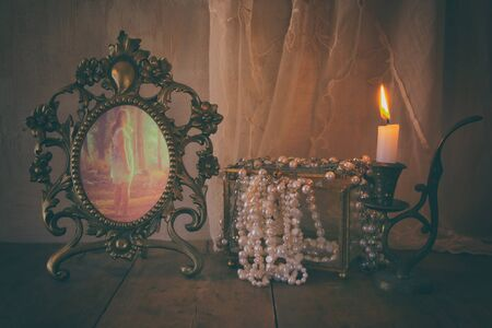 low key image of vintage frame with old photo, pearls and burning candle on wooden table. vintage filtered and toned Stock Photo