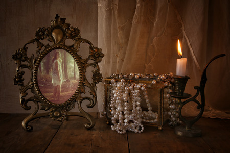 spirtual: low key image of vintage frame with old photo, pearls and burning candle on wooden table. vintage filtered and toned Stock Photo
