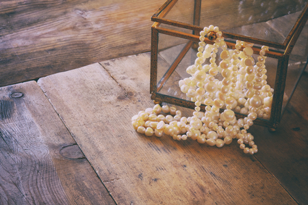 neckless: low key image of white pearls necklace on old grunge wooden table. vintage filtered and toned