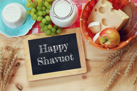 image of dairy products and fruits next to blackboard with the phrase: HAPPY SHAVUOT, on wooden background.