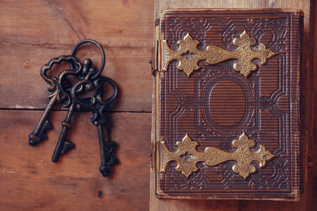 top view of antique book cover, with brass clasps and old keys. vintage filtered. selective focus