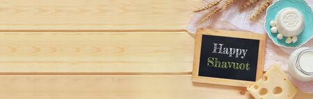 jewish holiday: website banner of dairy products on wooden background. Symbols of jewish holiday - Shavuot