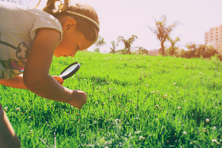 finding: cute kid (girl) looking and exploring nature in a park with a magnifying glass . retro style image Stock Photo