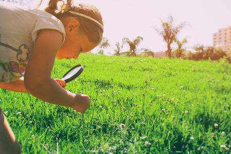 conclusion: cute niño (niña) buscando y explorando la naturaleza en un parque con una lupa. imagen de estilo retro Foto de archivo