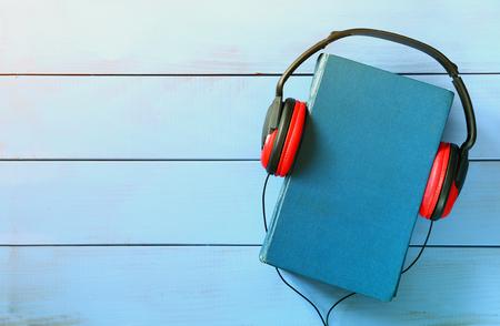 オーディオ ブックのコンセプト、青表紙本と木製のテーブルの上のヘッドフォンの平面図