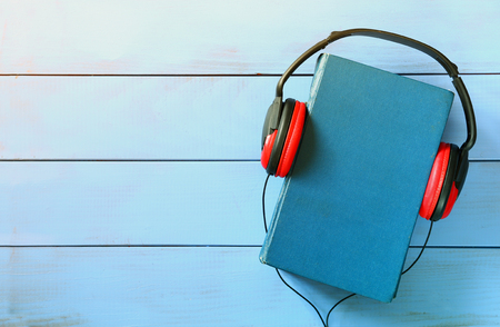 top view of audio book concept, blue cover book and headphones over wooden table Foto de archivo