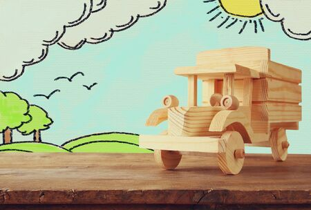 wooden toy: photo of wooden toy car over wooden table and counrtside landscape sketch background. travel and and vacation concept Stock Photo