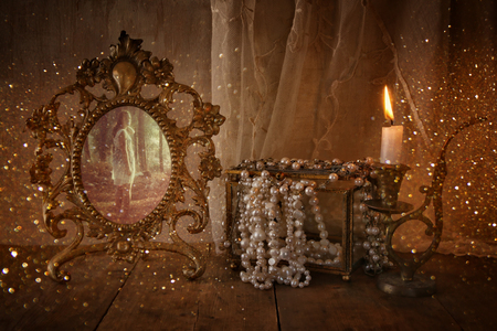 neckless: low key image of vintage frame with old photo, pearls and burning candle on wooden table. vintage filtered and toned with glitter overlay