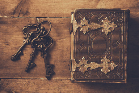 clasps: top view of antique book cover, with brass clasps and old keys. sepia vintage filtered. selective focus