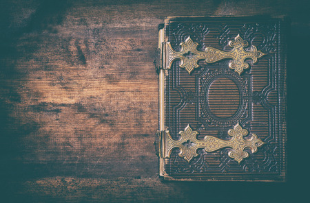 clasps: low key image of top view of antique book cover, with brass clasps. vintage filtered and toned