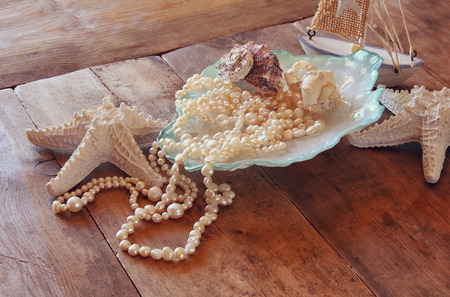 sea shell: image of white pearls necklace and seashells on old grunge wooden table. vintage filtered