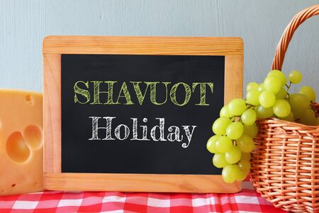 shavuot: image of dairy products and fruits next to blackboard, on wooden background. Symbols of jewish holiday - Shavuot