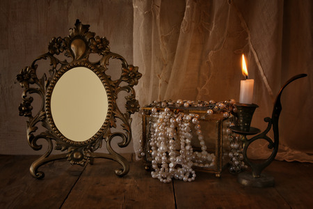 once person: low key image of blank vintage frame, pearls and burning candle on wooden table. vintage filtered and toned Stock Photo