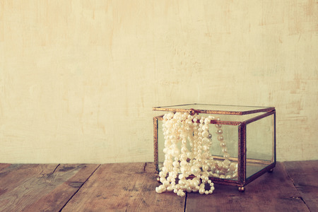 neckless: white pearls necklace on old grunge wooden table. vintage filtered and toned Stock Photo