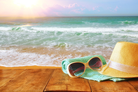 fedora: fedora hat and sunglasses over wooden table and sea landscape background. relaxation or vacation concept