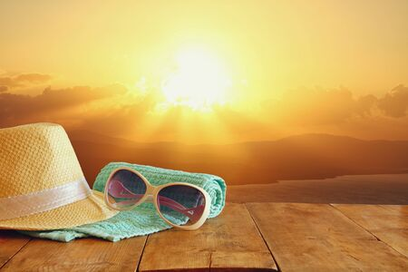 fedora: fedora hat and sunglasses over wooden table and sunset landscape background. relaxation or vacation concept Stock Photo