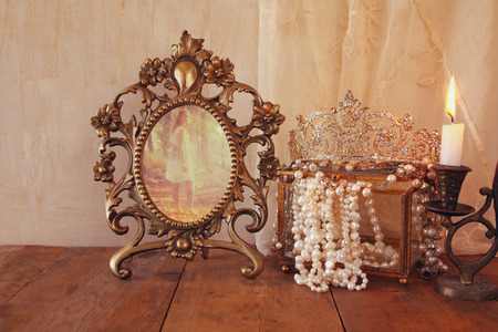 once: image of vintage frame with old photo, pearls and burning candle on wooden table. vintage filtered