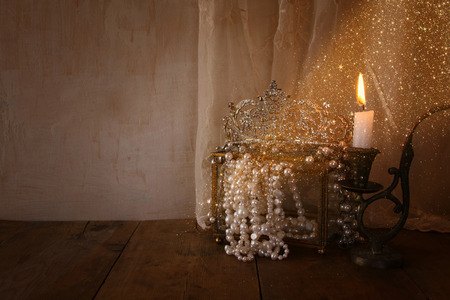 diamond candle: low key image of beautiful diamond queen crown, white pearls next to burning candle. vintage filtered with glitter overlay. fantasy middle age concept