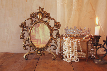 neckless: image of vintage frame with old photo, pearls and burning candle on wooden table. vintage filtered