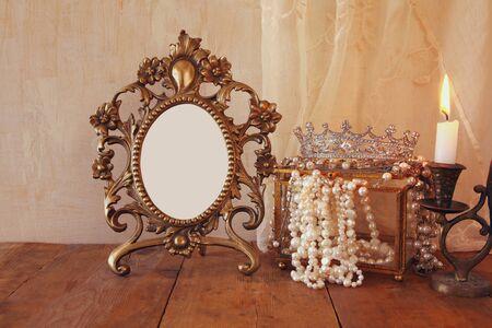 fantasy background: image of blank vintage frame, pearls and burning candle on wooden table. vintage filtered