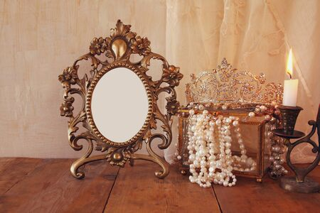 neckless: image of blank vintage frame, pearls and burning candle on wooden table. vintage filtered