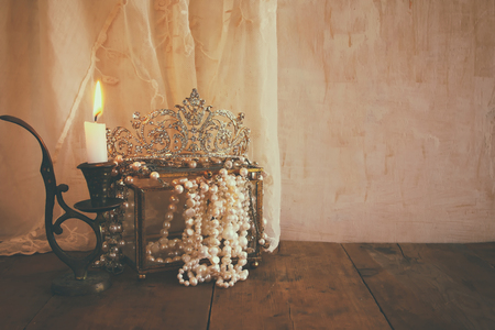 diamond candle: low key image of beautiful diamond queen crown, white pearls next to burning candle. vintage filtered and toned. fantasy middle age concept