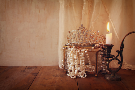 diamond candle: low key image of beautiful diamond queen crown, white pearls next to burning candle. vintage filtered. fantasy middle age concept